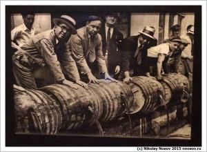 Мужчины выливают вино из бочек